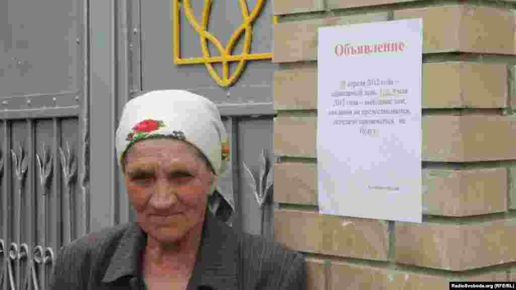 Жінка прийшла передати харчі до колонії стоїть на фоні оголошення