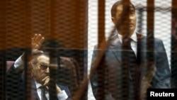 Бывший президент Египта Хосни Мубарак (слева) машет своим сторонникам в зале суда, один из его сыновей Алаа в клетке в зале суда в Каире, 9 мая 2015 года.