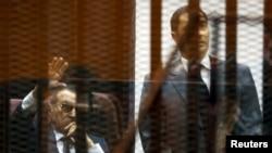الرئيس المصري الاسبق حسني مبارك يلوح لمؤيديه من قفصه اثناء محاكمته مع نجليه علاء وجمال، 9 آيار 2015.