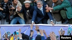 Presidential candidate Abdullah Abdullah shakes hands with his supporters during an election campaign in Kabul.