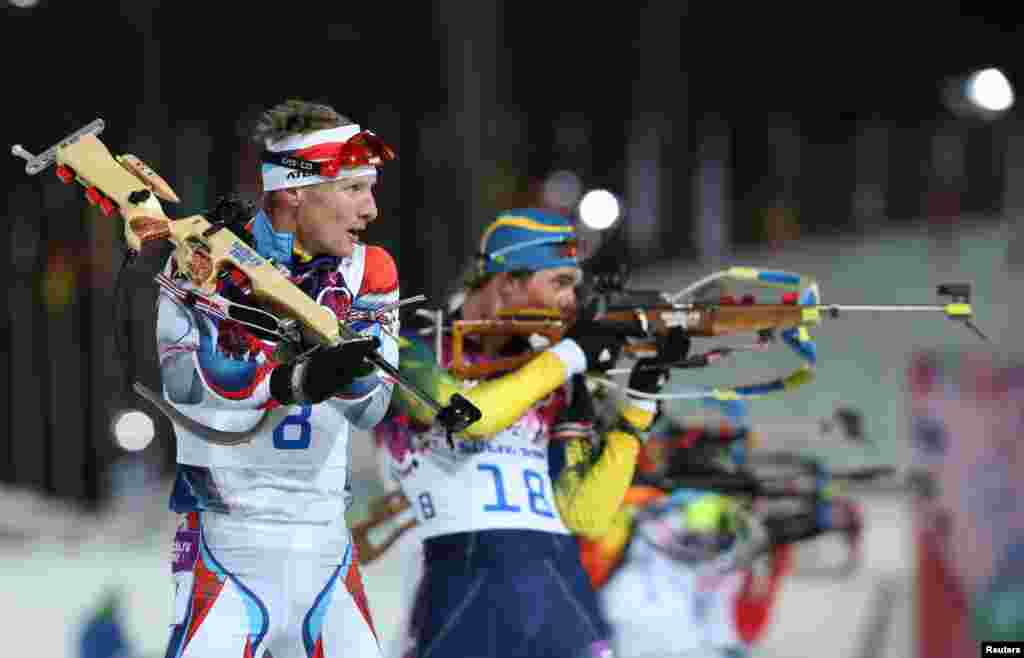 The Czech Republic's Ondrej Moravec stands next to Sweden's Fredrik Lindstroem (right) at the shooting range during the men's biathlon 12.5-kilometers pursuit event. Martin Fourcade of France won the gold medal. Moravec took silver, and France's Jean-Guillaume Beatrix won the bronze.
