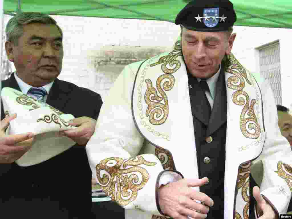 General David Petraeus, the head of U.S. Central Command, tries on Kyrgyz national dress in Shopokove, near Bishkek. - Petraeus visited Kyrgyzstan on March 11 to discuss counterterror efforts and cooperation in fighting the insurgency in Afghanistan. Photo by Vladimir Pirogov for Reuters