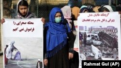 FILE: Afghan women activists hold banners highlighting alleged Taliban atrocities.