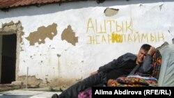 """Әлеуметтік мәселелерін шеше алмаған оралман Аманбай Аңдабаев қабырғаға """"Аштық жариялаймын"""" деп жазып қойып, өзі далада жатыр. Ақтөбе, 5 тамыз 2011 жыл."""