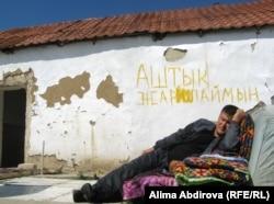 """Оралман Аманбай Андабаев лежит на фоне надписи """"Объявляю голодовку"""". Актобе, 5 августа 2011 года."""