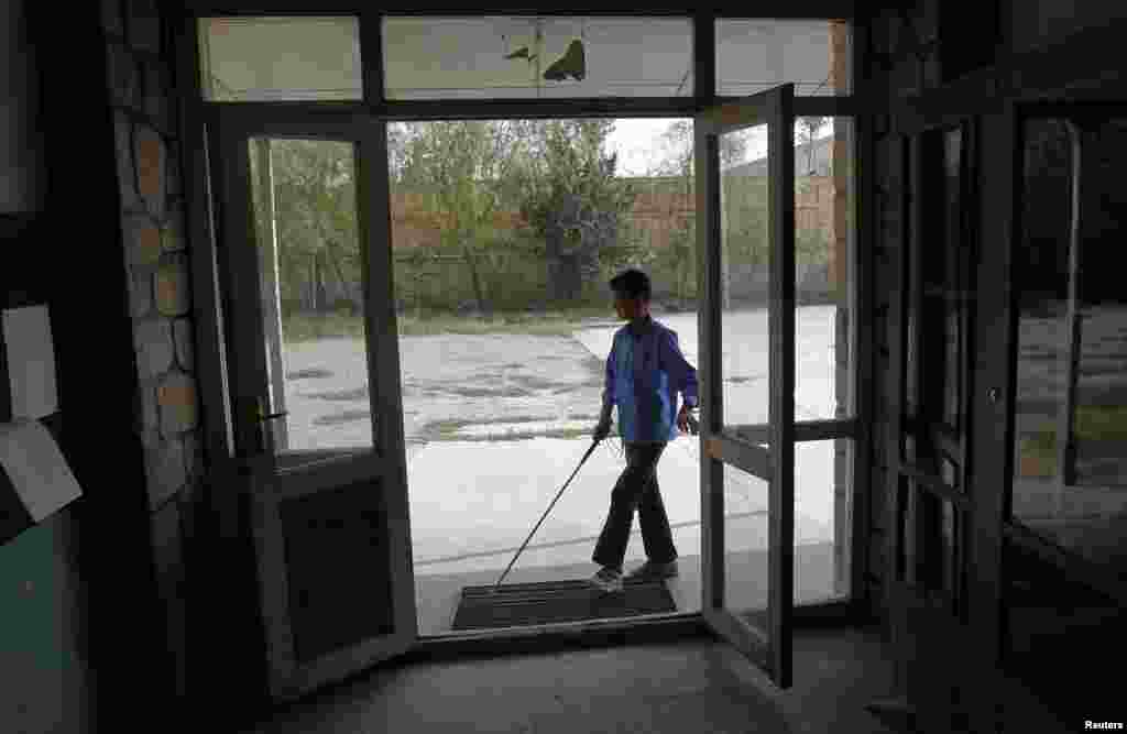 A blind student arrives for a lesson at the Kabul Blind School.