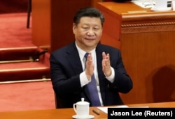 Chinese President Xi Jinping applauds after parliament passed a constitutional amendment lifting presidential term limits.