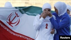 An Iranian women's national soccer player is comforted in Amman by a teammate after withdrawing from their June qualifying match against Jordan for the 2012 London Olympic Games.