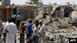 Iraqis stand amid the rubble of destroyed houses following a series of bomb attacks in the country on July 23.