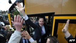 The leader of the Liberal Democrats, Nick Clegg, waves from his campaign bus as he leaves a rally in London.