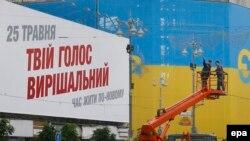 """Сотрудники коммунальных служб на фоне плаката с надписью: """"Твой голос - решающий"""". Киев, 21 мая 2014 года."""
