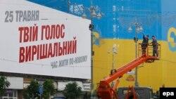 Сайлауға дауыс беруге шақырған жазудың жанында тұрған коммуналдық қызмет жұмысшылары. Киев, 21 мамыр 2014 жыл.