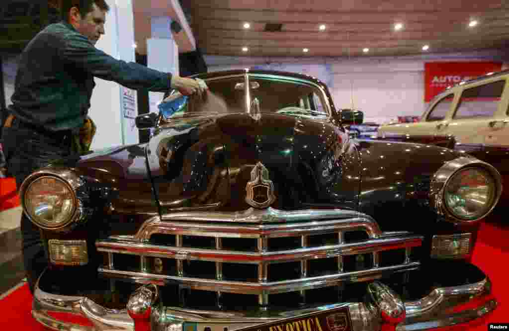 A man cleans his vintage Soviet-made GAZ-12 ZIM during a retro car show in Kyiv. (Reuters/Sergiy Polezhaka)