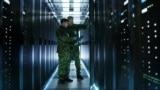 Doi militari într-o încăpere unde sunt ţinute mai multe servere