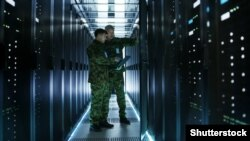 GENERIC – In Data Center Two Military Men Work with Open Server Rack Cabinet. One Holds Military Edition Laptop.