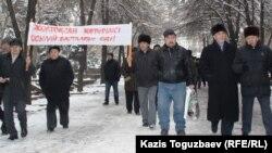 """Политик Хасен Кожа-Ахмет и его сторонники идут к офису президентской партии """"Нур Отан"""", чтобы выразить протест действиям властям в Жанаозене, где в массовых беспорядках 16 декабря 2011 года погибли 10 человек."""