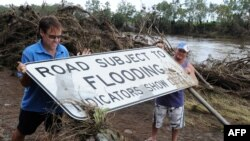 Residents near the town of Gin Gin restore a flood-warning sign next to the swollen Burnett River in eastern Australia on January 2.