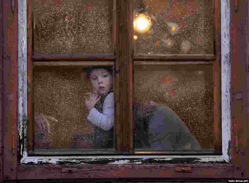 A child peers from a rain-covered window in the Transylvanian town of Sibiu, Romania. (AP/Vadim Ghirda)