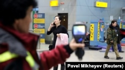 A Kazakh sanitary-epidemiological service worker uses a thermal scanner to detect travelers from China who may have coronavirus symptoms at Almaty's airport on January 21.