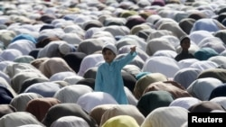 A boy stands amidst Muslims performing the Eid al-Adha prayer in Karachi on September 25.