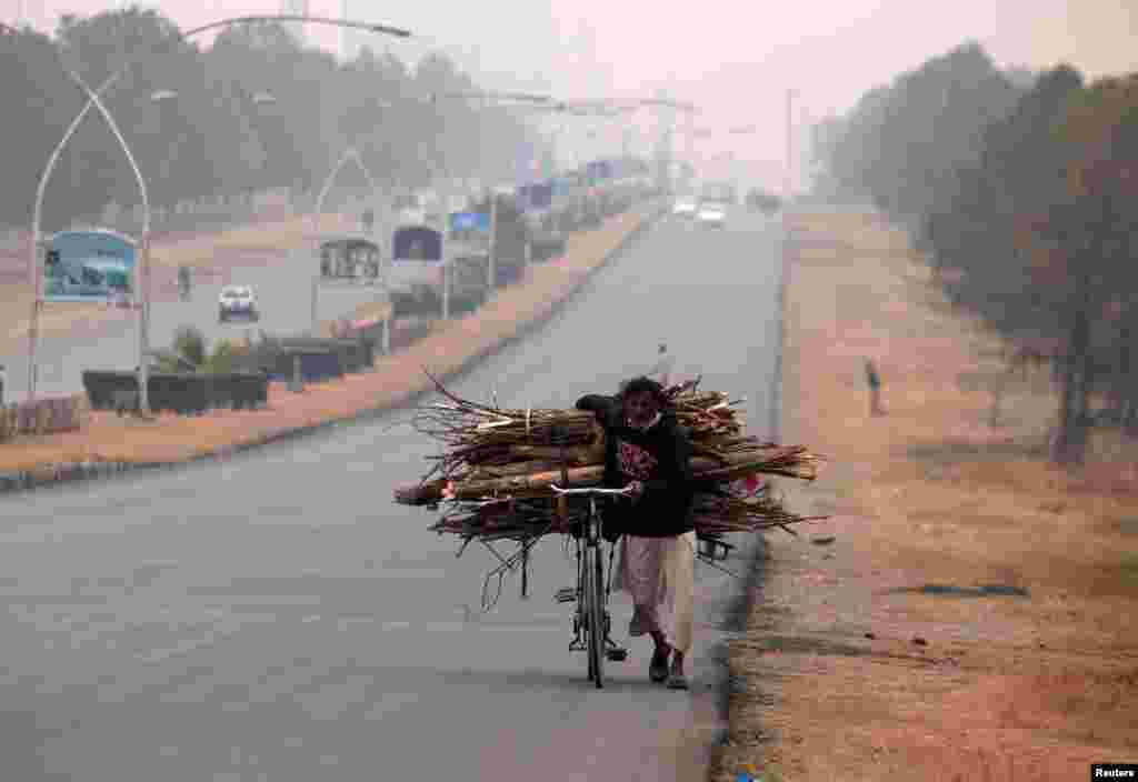 A man pushes a bicycle loaded with tree branches to be used for heating and cooking on a road in Islamabad, Pakistan. (Reuters/Faisal Mahmood )
