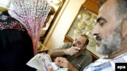 Iraq - A goldsmith speaks with his customers at a shop in the Karada district of Baghdad, 14Oct2008