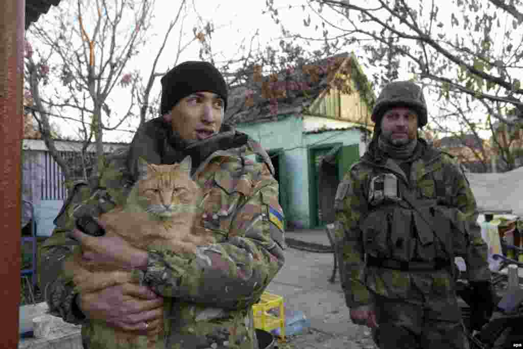 Ukrainian serviceman play with a cat during a short break in the village of Pesky, not far from the embattled airport of Donetsk, in October 2014.