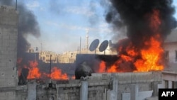 Flames are seen on the roof of a building in the Baba Amr neighborhood of the flash-point city of Homs during the bombardment of the city on February 22.