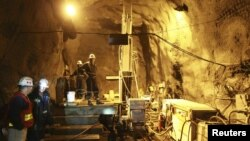 Workers stand beside machinery in a tunnel in the Kumtor mine.