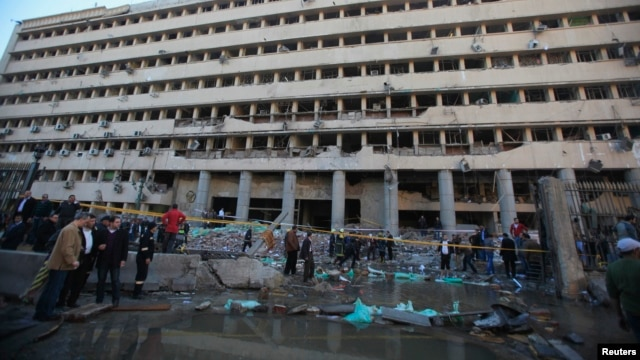 Police officers and others gather in front of the damaged Cairo Security Directorate, which includes police and state security, after a bomb attack on January 24.