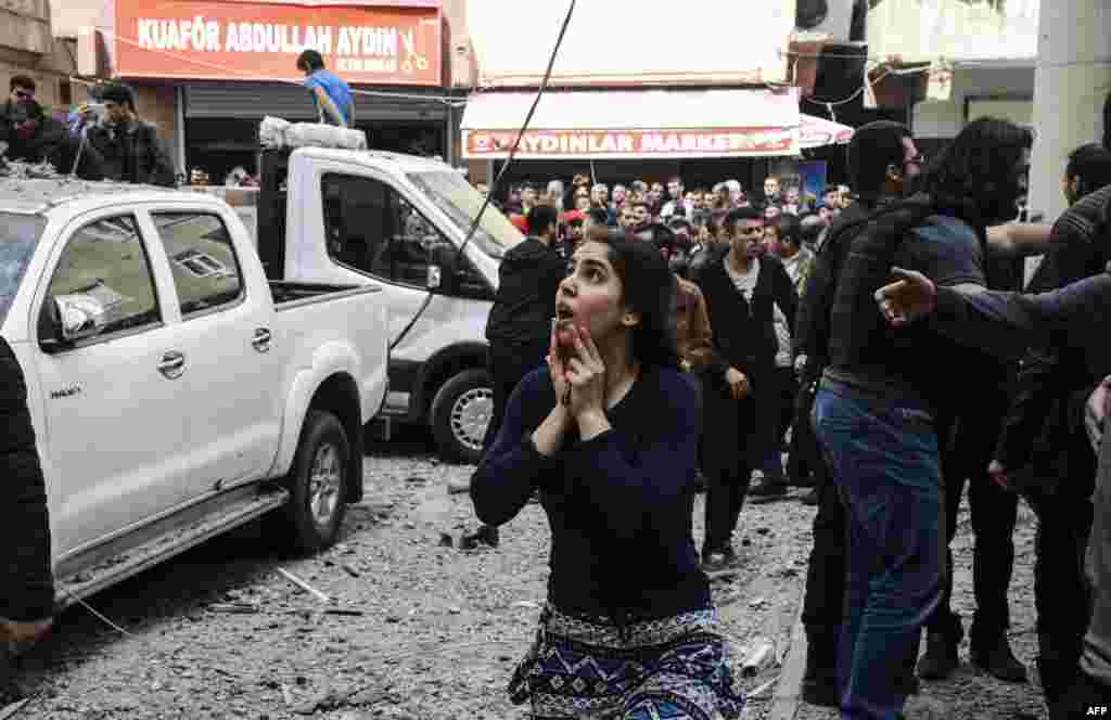 A woman reacts as she looks at the site of a strong blast near the riot-police headquarters in the center of Diyarbakir, Turkey, on April 11. (AFP/Ilyas Akengin)