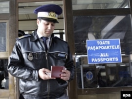 A customs officer checks a passport at the Romanian border with Moldova in Albita. (file photo)