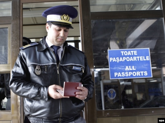 A Romanian customs officer checks a passport at the border with Moldova in Albita.