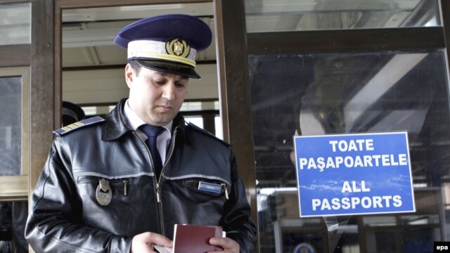 A Romanian customs officer checks a passport at the border with Moldova in Albita. The EU's eastern border divides the two neighbors.