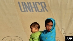 An internally displaced girl carries a child at a makeshift tent camp in Swabi on May 25.