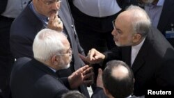 IIranian Foreign Minister Mohammad Javad Zarif (left) and head of the Atomic Energy Organization of Iran Ali Akbar Salehi (right) appear to have an intense discussion on the sidelines of negotiations with U.S. Secretary of State John Kerry over Tehran's nuclear program in Lausanne, Switzerland.