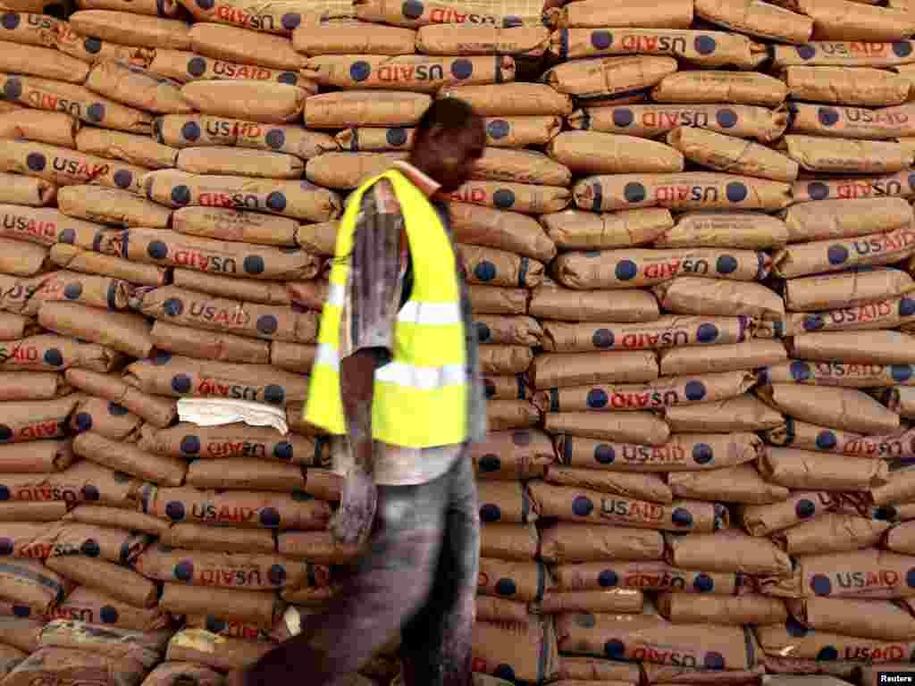 Працівник Всесвітньої продовольчої програми проходить повз мішків з гуманітарною допомогою у розподільному центрі в таборі для біженців Дадаабе неподалік кордону між Кенією та Сомалі, 1 серпня. Посухи та збройні конфлікти поглиблюють продовольчу кризу в Африці. Photo by Thomas Mukoya for Reuters