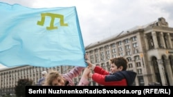 Copii care flutură un steag al tătarilor din Crimeea, în Kiev pe 18 martie când se marchează ziua de amintire a tătarilor din Crimeea care au fost deportați în Centrul Asiei și Siberia în 1944. Zeci de mii au murit în timpul deportărilor în masă, care au fost recunoscute de Ucraina drept un genocid. (Serhii Nuzhnenko, RFE/RL)