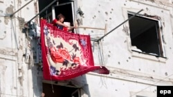 A woman dries a carpet after returning to her bullet-riddled home in Tskhinvali in August 2008.