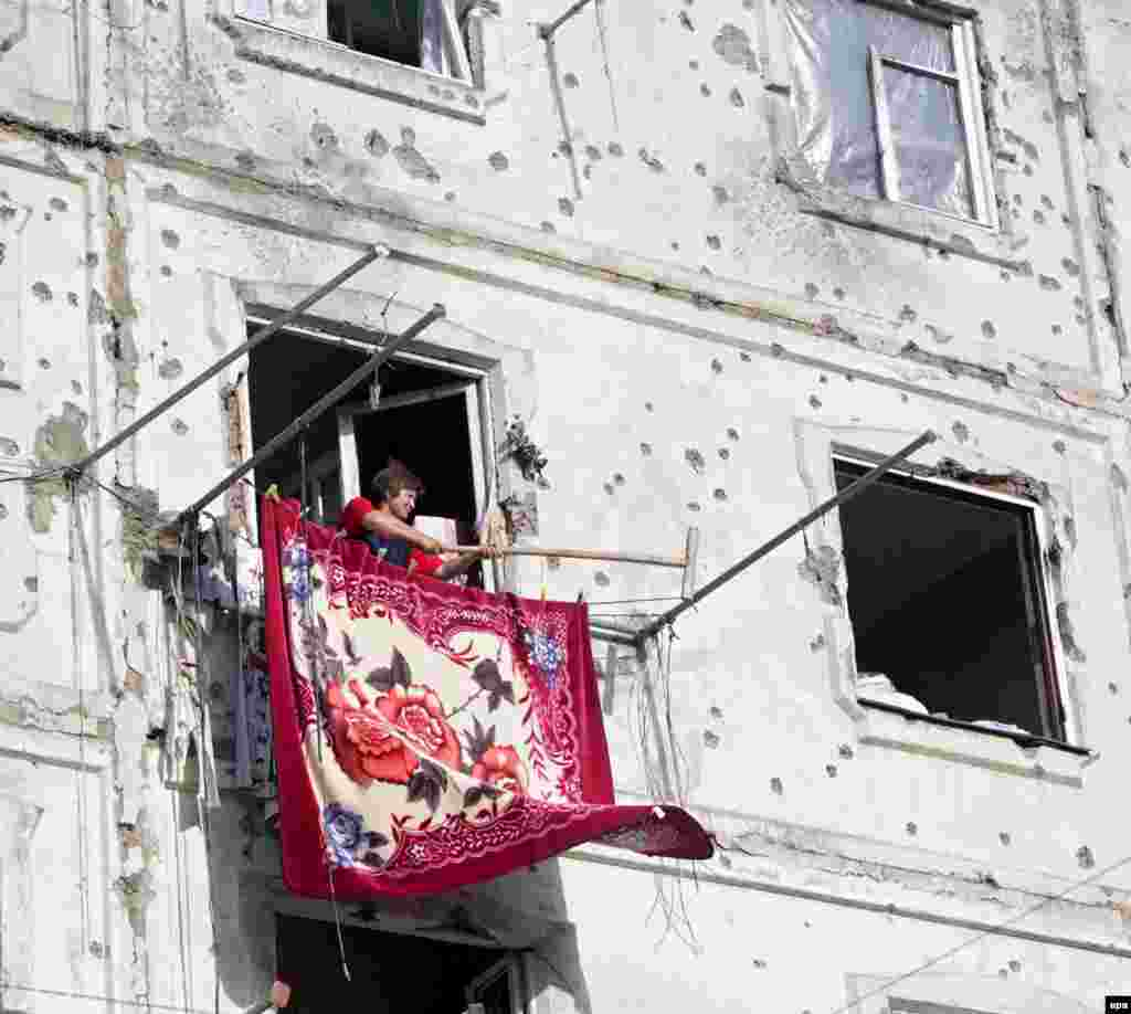 A woman hangs out a carpet as she returns to her destroyed home in Tskhinvali, the capital of South Ossetia, on August 23, a week after the end of the fighting.