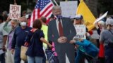 USA -- A cardboard cutout of U.S. President Donald Trump wearing a mask is brought to a protest over the stay-at-home orders involving the closing of beaches and walking paths during the outbreak of the coronavirus disease (COVID-19) in Encinitas, Califor