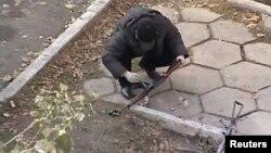 Полицей террорлық шабуылдан кейін табылған қаруды тексеріп жатыр. Тараз, 12 қараша 2011 жыл.
