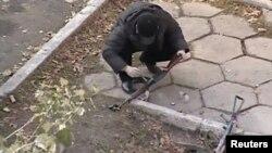 Оқиға орнынан табылған қаруларды тергеуші тексеріп жатыр. Тараз, 12 қараша 2011 жыл.