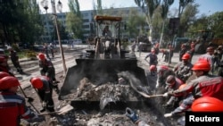 Metinvest workers remove barricades and debris in front of the City Hall in Mariupol