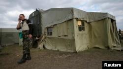 Український військовий розмовляє по телефону біля польового шпиталю у Сватові, вересень 2014 року