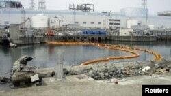 Желтое плавучее заграждение должно препятствовать распространению радиоактивной воды