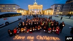 "Demonstrators call for the international community to ""Save the Children in Syria"" and hold a minute of silence in front of the Brandenburg Gate in Berlin on March 14."