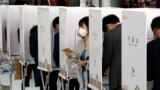 A woman leaves a voting booth to cast her ballot for the parliamentary elections at a polling station in Seoul on April 10.