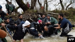 A refugee family falls into a river they try to cross to reach Macedonia from a makeshift camp near the Greek border village of Idomeni.