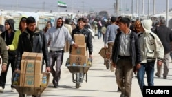 Syrian refugees in Jordan collect aid and rations at the Al-Zaatri refugee camp in the city of Mafraq near the border with Syria on March 6.